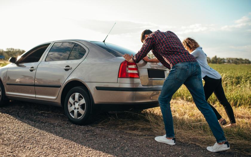 ผุ้ชายกับผู้หญิงช่วยกันเข็นรถยนต์